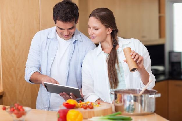 In den liebespaaren, die einen tablet-computer verwenden, um zu kochen