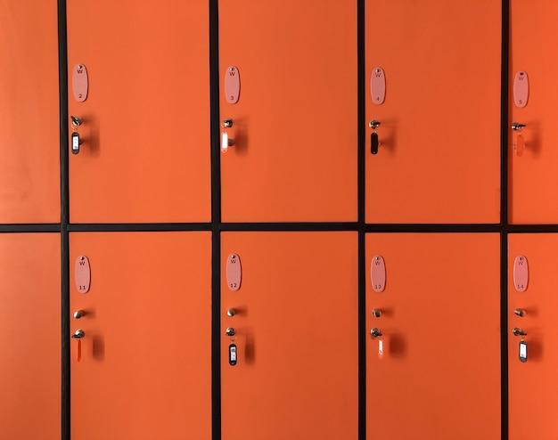 In den orangefarbenen schließfächern im fitnessstudio sind viele türen mit schlüsseln für die private sicherheit verschlossen