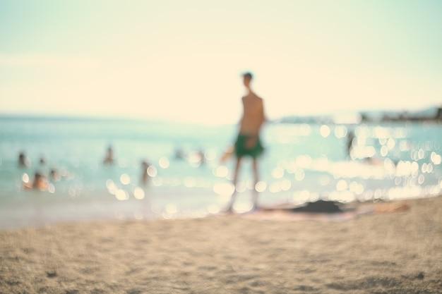 In den sommerferien. schattenbild eines mannes, der tennis auf dem strand spielt.