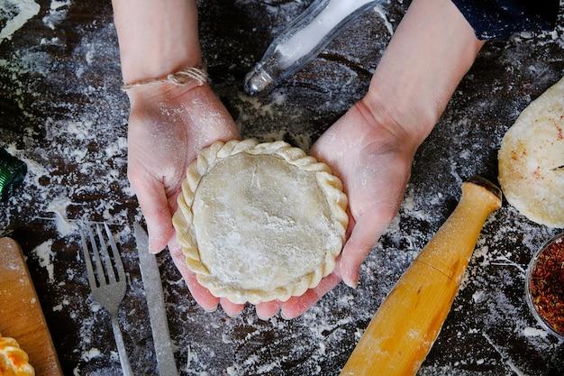 In den weiblichen händen der köchin befindet sich eine torte, ein kuchen aus rohem teig. in der nähe von küchenutensilien. konzept des kochens und backens, hauptbäckerei.