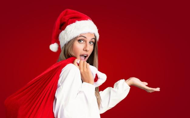 In den weihnachtsferien junge blonde frau, die eine tasche voll der geschenke über getrennter roter wand aufhebt
