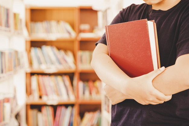 In der bibliothek - junge studentin mit büchern, die in einer high school-bibliothek arbeiten.
