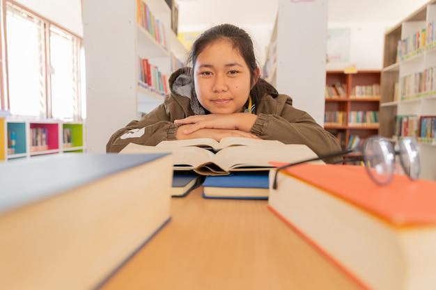 In der bibliothek - junge studentin mit büchern, die in einer highschool-bibliothek arbeiten.