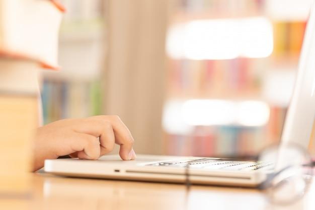 In der bibliothek - yfocused student, der computer in einer bibliothek verwendet
