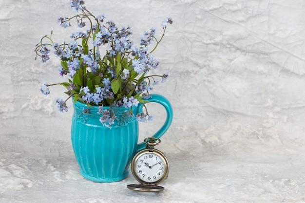 In der blauen alten tasse ein strauß vergissmeinnichte und eine taschenuhr