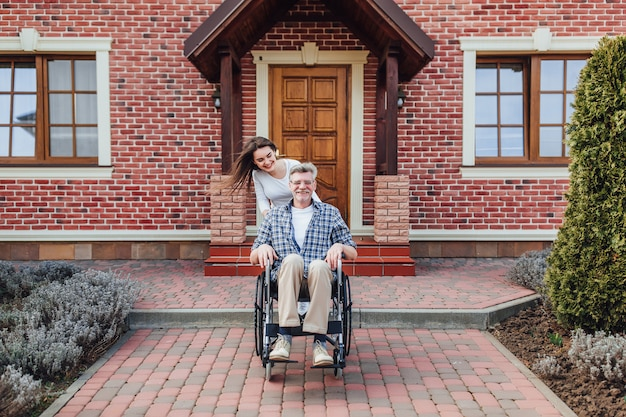 In der familienzeit genießen älterer mann im rollstuhl und lächelnde tochter im garten