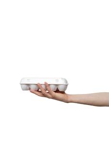In der hand gehaltene eier lokalisiert auf weißem hintergrund. mann hält plastikverpackung