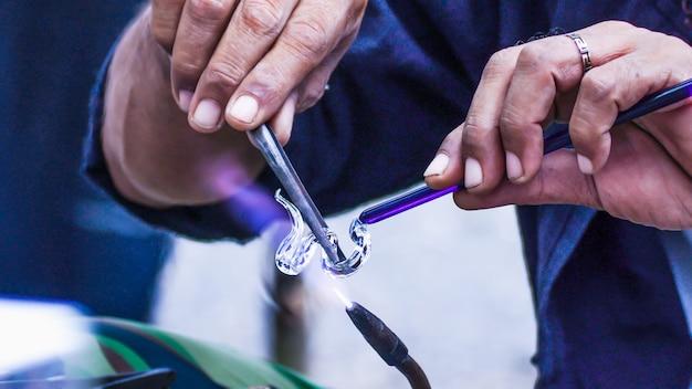 In der hand halten die stahlstange und das glas das mundgeblasene glas. sprühen sie mit hitze glas, um verschiedene formen zu erhalten