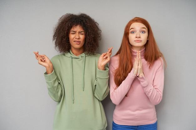 In der hoffnung, dass junge schöne frauen ihre hände heben, während sie wünsche machen, für ihre träume beten, während sie an einer grauen wand stehen