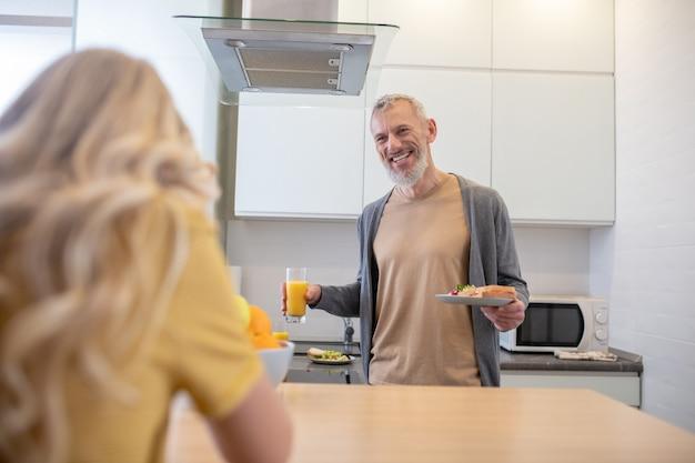 In der küche. ein reifer mann und seine tochter unterhalten sich in der küche