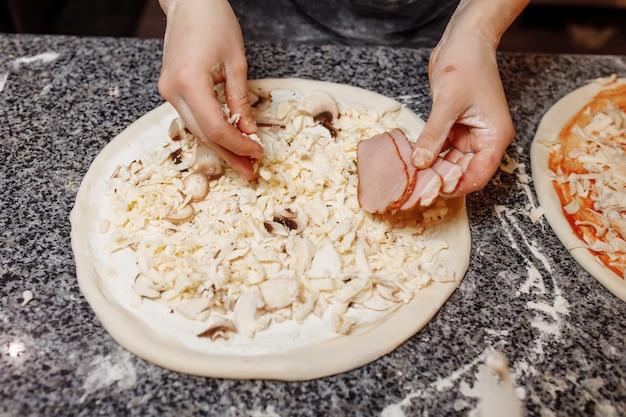 In der küche kochen und die zutaten auf die pizza geben. pizza-konzept. produktion und lieferung von lebensmitteln.