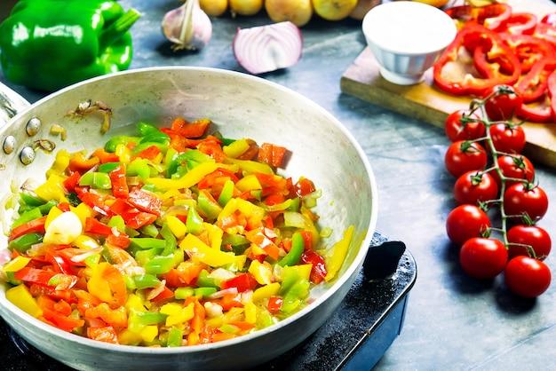 In der küche mit gehackten bunten paprikaschoten schwenken, um eine pasta-gewürzsommersauce zuzubereiten