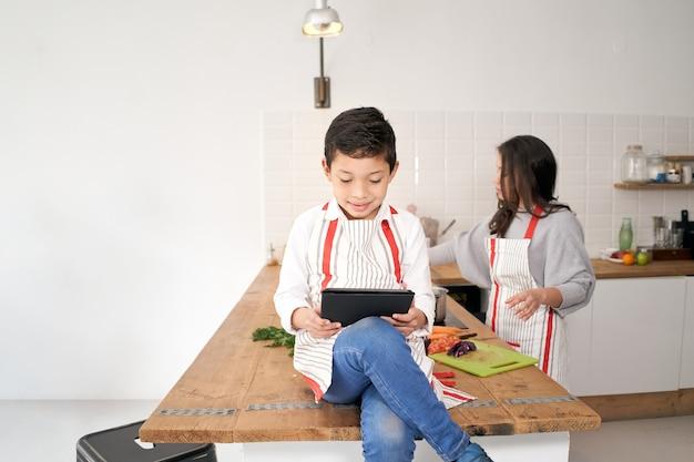 In der küche spielt ein kind mit einem tablet videospiele, während seine mutter gemüse für das essen schneidet...