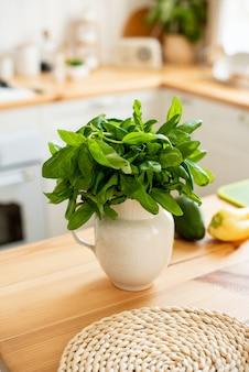In der küche stehen spinatblätter in einer vase. gesundes lebensmittelkonzept. das mädchen bereitet einen leichten gesunden sommersalat zu.