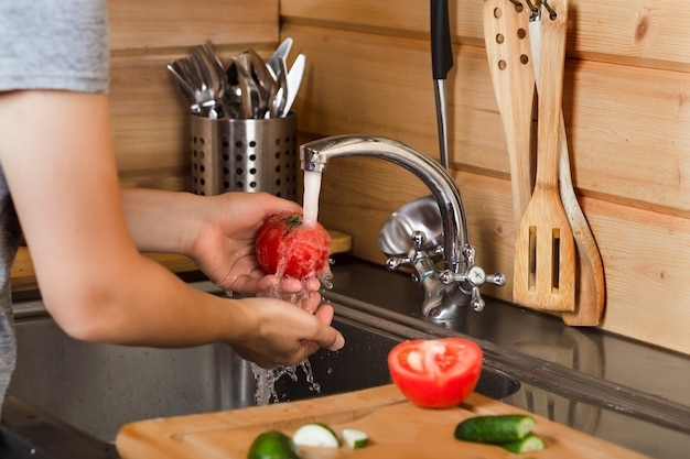 In der küche unter fließendem wasser die hände der frauen waschen reife tomaten