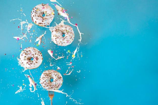 In der luft schwebende donuts auf einem blauen hintergrund. süßigkeiten, gebäck.