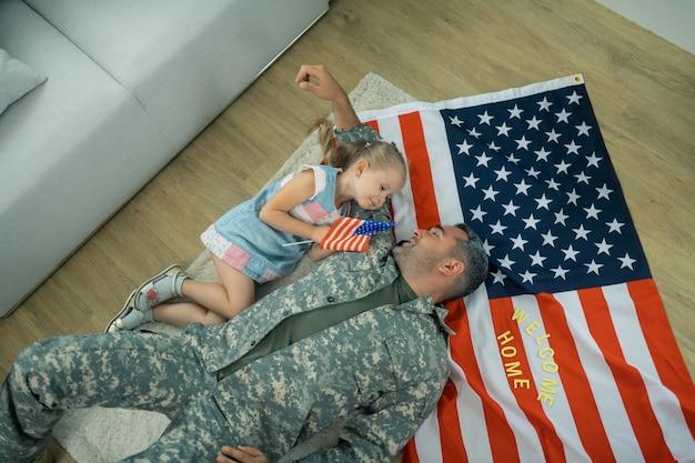 In der nähe der tochter liegen. militärdiener auf dem boden liegend mit amerikanischer flagge in der nähe seiner süßen schönen tochter floor