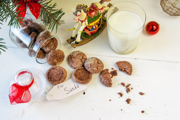 In der nähe der weihnachtsdekoration gingen ein glas milch und kekse speziell für den weihnachtsmann.