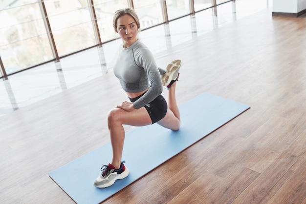 In der nähe des großen fensters. sportliche junge frau haben fitness-tag im fitnessstudio zur morgenzeit