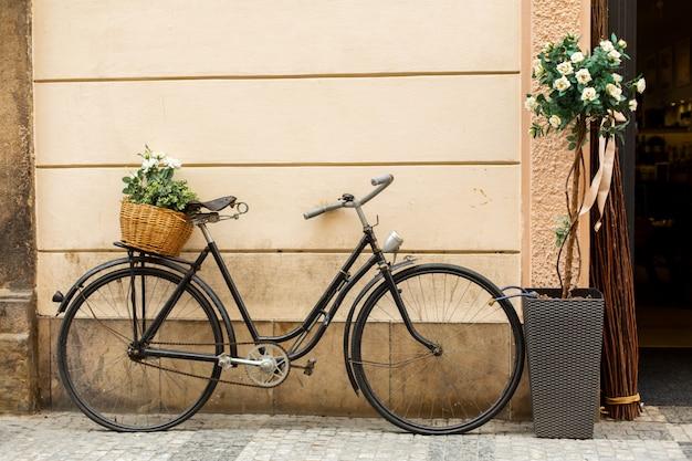In der nähe des hauseingangs steht ein fahrrad mit einem korb mit frischen blumen im alten europäischen stil