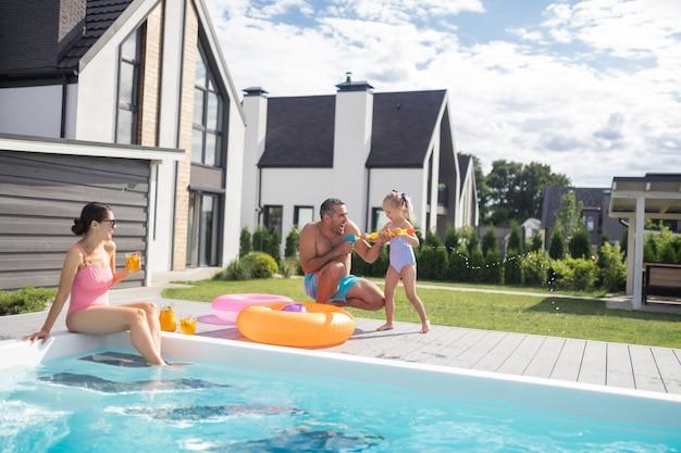 In der nähe eines privaten pools. schöne süße tochter, die aufgeregt ist und spaß mit den eltern in der nähe des privaten pools hat?