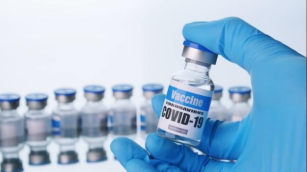 In der nähe hält der wissenschaftler eine glasflasche für den covid-19-impfstoff im labor