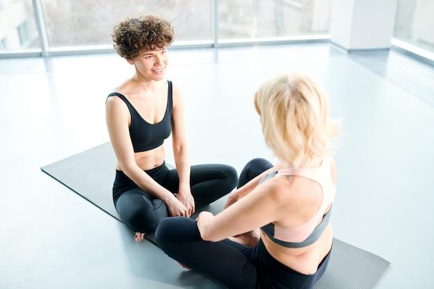In der pause chatten. frauen auf matte machen yoga neben einem großen fenster
