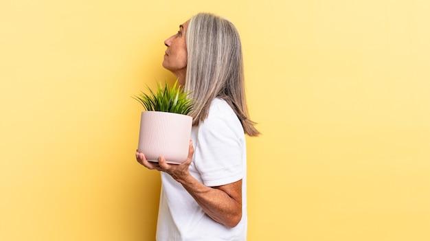In der profilansicht, um den raum vor ihnen zu kopieren, nachzudenken, sich vorzustellen oder zu träumen, eine dekorative pflanze zu halten
