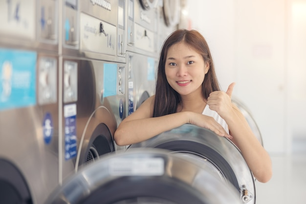 In der sb-wäscherei mit trocknermaschinen im hintergrund genießt eine junge frau sauber gebügelte kleidungsstücke.