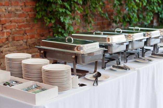In der schlange stehende beheizte buffetschalen stehen bereit. im freien buffetrestaurant, das hotelrestaurant.