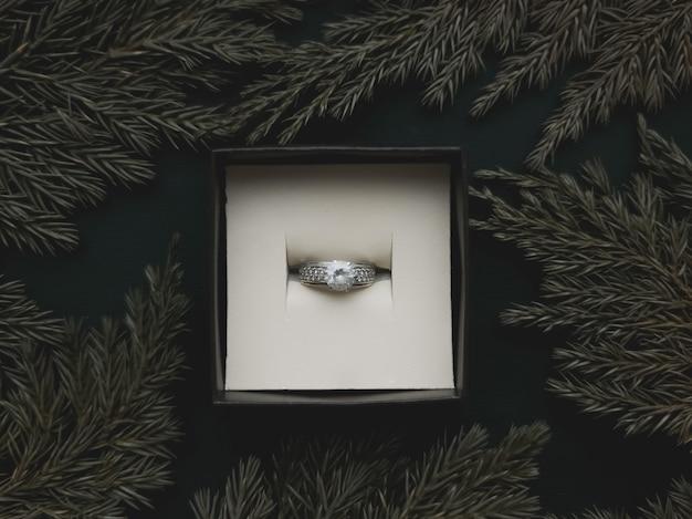 In der schmuckschatulle befindet sich ein ring mit einem rahmen aus wacholderzweigen auf einem schönen schwarzen hintergrund. romantisches konzept. flacher stil.