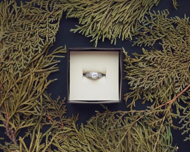 In der schmuckschatulle befindet sich ein ring mit einem rahmen aus zypressenzweigen auf einem schönen schwarzen hintergrund. romantisches konzept. flacher stil.