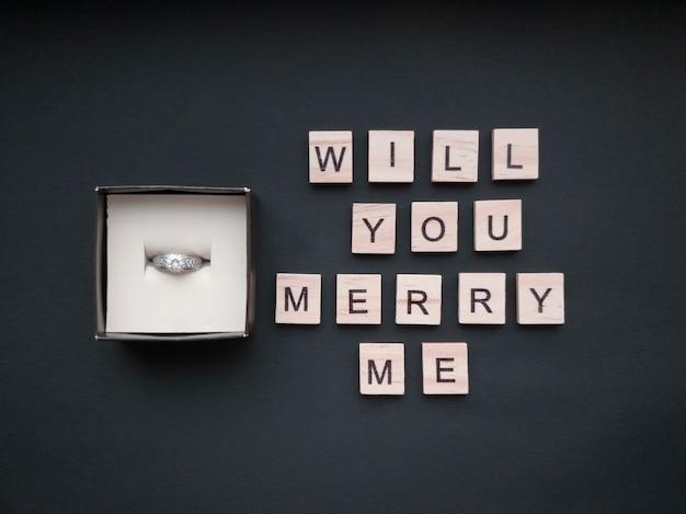 In der schmuckschatulle befindet sich ein ring mit einem stein und einer aufschrift aus holzquadraten auf einem wunderschönen schwarzen hintergrund. romantisches konzept. flacher stil.