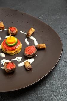 In der vorderansicht gekochte kürbisse gestalteten mahlzeit innerhalb platte auf grauem raum