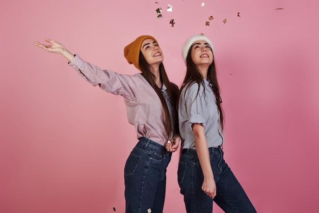 In die luft schauen. neujahrskonzeption. zwei zwillinge spielen und werfen goldenes konfetti in die luft