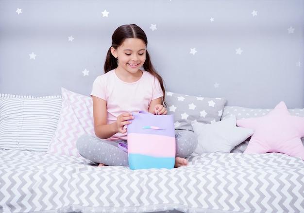 In dieser tasche bewahrt sie ihre schätze auf. mädchen sitzen auf dem bett in ihrem schlafzimmer. kind bereiten sich vor, ins bett zu gehen. angenehme zeit im gemütlichen schlafzimmer. mädchen kind lange haare süße pyjamas im schlafzimmer entspannen.