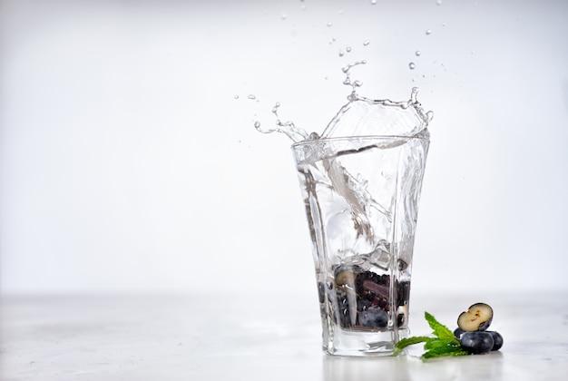 In ein glas mit eingegossenem wasser mit beeren und minze spritzen