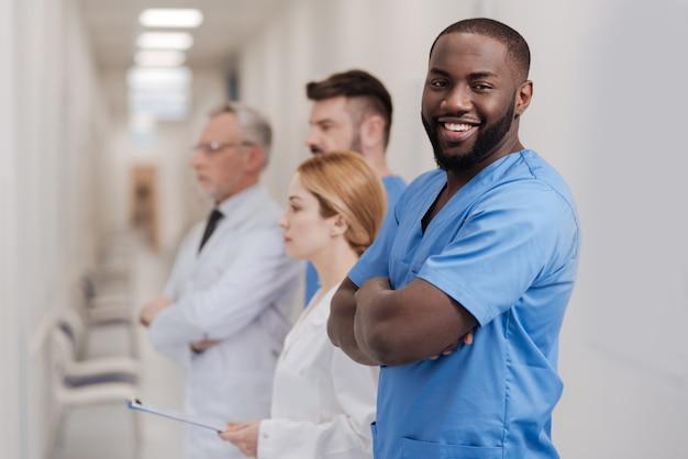 In eine richtung schauen. lächelnder begabter afroamerikanischer praktikant, der den untersuchungsprozess in der klinik genießt und mit verschränkten armen steht, während andere kollegen stehen