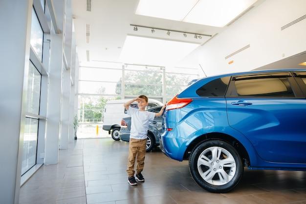 In einem autohaus steht ein glücklicher junge in der nähe eines neuen autos, bevor er es kauft