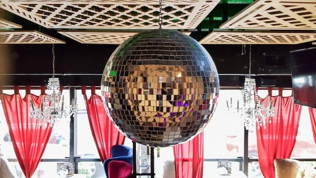 In einem café oder restaurant hängt eine discokugel von der decke. restaurantinnenraum mit holzdecke und roten vorhängen.