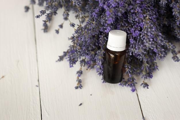 In einem lila blumenstrauß steht ein dunkles glas mit ätherischem lavendelöl. draufsicht