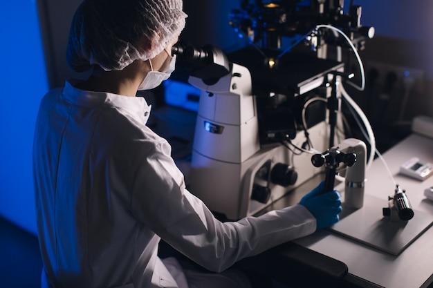In einem modernen labor führen wissenschaftler experimente durch. der embryologe untersucht proben mit einem mikroskop