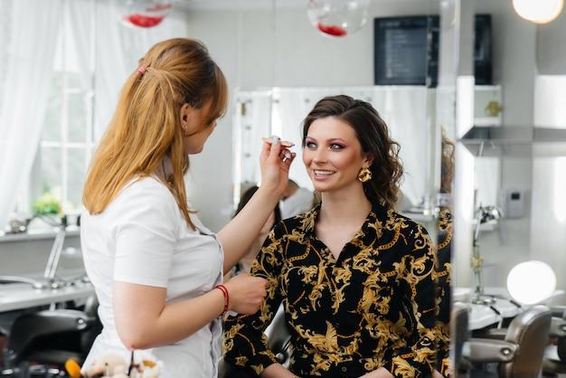 In einem schönen, modernen schönheitssalon macht ein professioneller make-up-stylist make-up für ein junges mädchen. schönheit und mode.