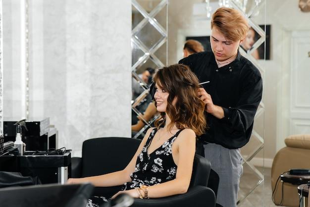In einem schönen, modernen schönheitssalon macht ein professioneller stylist einen haarschnitt und eine frisur für ein junges mädchen. schönheit und mode.