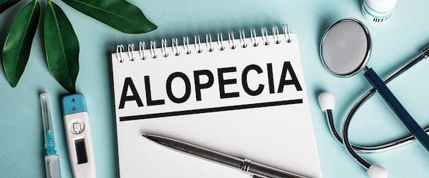 In einem weißen notizbuch auf einer blauen oberfläche neben einem blatt sheffler, einem stethoskop, einer spritze und einem elektronischen thermometer steht das wort alopecia