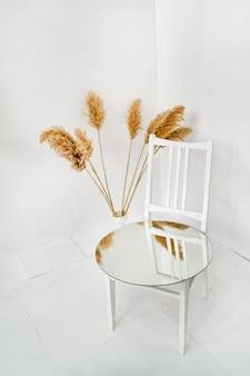 In einem weißen raum steht ein weißer holzstuhl mit getrockneten pflanzen und einem spiegel darauf. rustikal, boho, minimalistisches innendesign. foto in hoher qualität