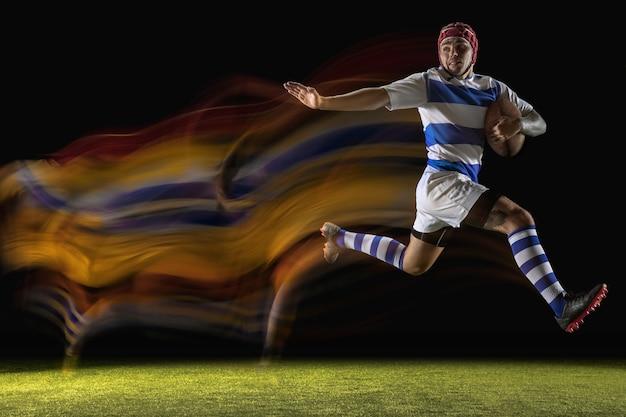 In einem wichtigen moment gefangen. ein kaukasischer mann, der rugby auf dem stadion in gemischtem licht spielt.