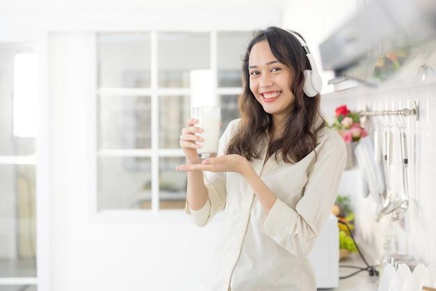 In einer hellen modernen küche trinkt eine schöne frau milch, während sie musik hört. vor dem frühstück amüsiert sie sich und lächelt.