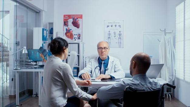 In einer modernen klinik für behinderte und behinderte genesung sucht ein junger mann im rollstuhl beratung und behandlung. behandlung von behinderten mit behinderungen in modernen privaten krankenhäusern oder kliniken