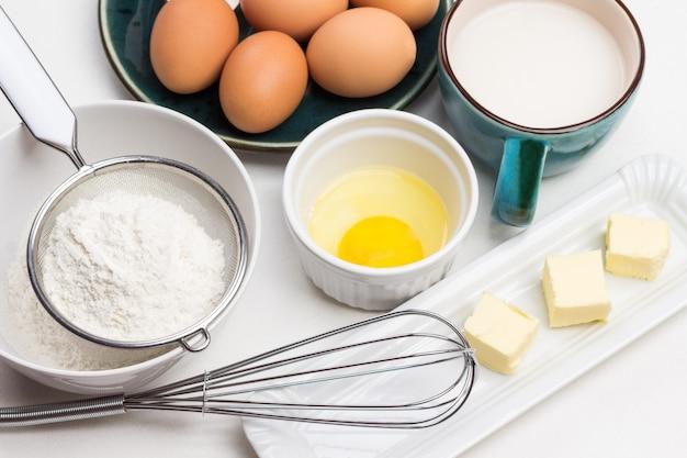 In einer schüssel verquirlen. mehl im sieb. gebrochenes ei in schüssel. butter auf teller. eier und milch im becher. draufsicht